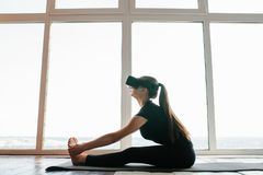 Uma menina bonita nova em vidros da realidade virtual faz a ioga e a ginástica aeróbica remotamente Conceito futuro da tecnologia Fotografia de Stock Royalty Free