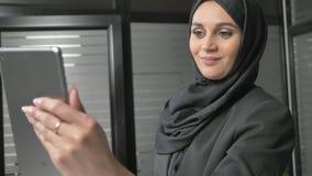 Uma menina bonita nova no hijab preto usa uma tabuleta, fala em um bate-papo video, cumprimentando 60 fps filme
