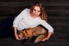 Uma menina bonita nova que guarda um animal selvagem da raposa que fosse traumatizado por um homem e salvado no seu e agora vidas Imagens de Stock