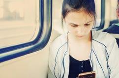 Uma menina bonita nova vai ao carro de trem e olha no smartphone imagens de stock royalty free