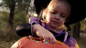 Uma menina bonita pequena em um traje e em um chapéu da bruxa toma doces da cubeta Dia das Bruxas no parque do outono vídeos de arquivo