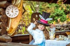 Uma menina bonita pequena que guarda o chapéu do cilindro com orelhas gosta de um coelho aéreo na tabela Fotografia de Stock Royalty Free