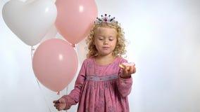 Uma menina bonita pequena três anos velha com balões come a filhós em seu aniversário, isolado sobre o fundo branco filme
