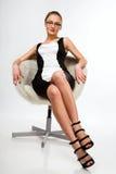 Uma menina bonita que senta-se em uma cadeira Fotos de Stock