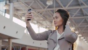 Uma menina bonita que toma o selfie no terminal de aeroporto Mulher de negócio nova na alameda com telefone Foto de Stock