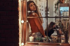 Uma menina bonita só que olha a câmera ao sentar-se em um peitoril da janela dentro do café fotos de stock royalty free
