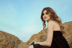 Uma menina bonita senta-se em uma ponte velha Fotografia de Stock