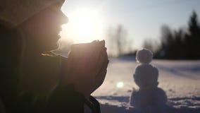 Uma menina bonita senta-se na rua com um copo de cozinhar o chá, aquece suas mãos, sorrisos, contra o contexto da vídeos de arquivo
