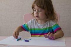 Uma menina bonita tira uma cor pastel colorida no Livro Branco A menina está sentando-se em uma cadeira na tabela Imagens de Stock Royalty Free