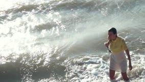 Uma menina bonita, triste em um vestido amarelo-branco e um cabelo louro, molhado longo saem do mar enlameado, enlameado É batida video estoque