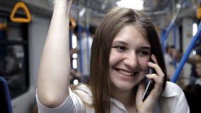 Uma menina bonita vai ao metro, guarda o corrimão e usa o telefone video estoque