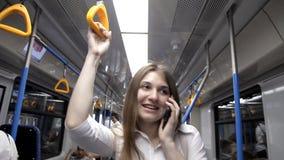 Uma menina bonita vai ao metro, guarda o corrimão e usa o telefone vídeos de arquivo