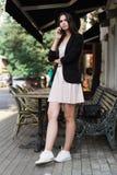 Uma menina bonita vestida em um vestido branco à moda, em um revestimento preto e em um chapéu negro está estando perto da mesa d fotografia de stock
