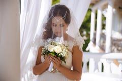 Uma menina bonita vestiu um vestido de casamento e um véu do laço, que cobrisse suas cabeça e cara, guardando com cuidado um casa fotografia de stock royalty free