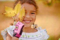 Uma menina bonito com cabelo escuro e os olhos marrons que sentam-se na grama e que olham na câmera, feliz e pensativo imagem de stock royalty free