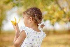Uma menina bonito com cabelo escuro e os olhos marrons que sentam-se na grama e que olham na câmera, feliz e pensativo imagem de stock