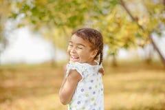 Uma menina bonito com cabelo escuro e os olhos marrons que sentam-se na grama e que olham na câmera, feliz e pensativo fotos de stock