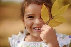 Uma menina bonito com cabelo escuro e os olhos marrons que sentam-se na grama e que olham na câmera, feliz e pensativo fotografia de stock