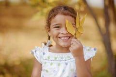 Uma menina bonito com cabelo escuro e os olhos marrons que sentam-se na grama e que olham na câmera, feliz e pensativo foto de stock