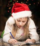 Uma menina bonito com entusiasmo escreve uma letra a Santa Fotografia de Stock