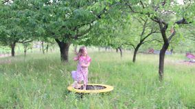 Uma menina bonito dança no jardim natural A menina dança e salta em um trampolim pequeno A menina veste floral video estoque
