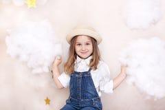 Uma menina bonito de sorriso voa no c?u com nuvens e estrelas Viajante pequeno de Little do astr?logo O conceito do edu pr?-escol imagens de stock royalty free