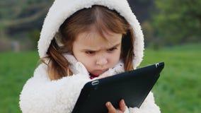 Uma menina bonito em uma capa branca engraçada está estudando a tabuleta vídeos de arquivo