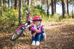 Uma menina bonito em um capacete que descansa ao lado de uma bicicleta em um dia ensolarado do verão Conceito da infância Conceit Fotografia de Stock Royalty Free