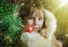 Uma menina bonito em um casaco de pele perto da árvore de Natal Foto de Stock