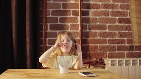 Uma menina bonito pequena come o iogurte de um grande frasco branco perto de uma parede de tijolo video estoque