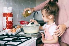 Uma menina bonito pequena e sua mãe que preparam a massa na cozinha em casa foto de stock