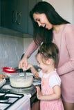 Uma menina bonito pequena e sua m?e que preparam a massa na cozinha em casa foto de stock