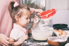 Uma menina bonito pequena e sua m?e que preparam a massa na cozinha em casa imagens de stock royalty free
