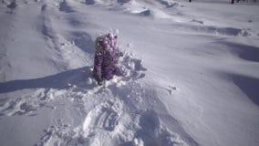 Uma menina bonito pequena que joga com neve no parque do inverno video estoque