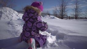 Uma menina bonito pequena que joga com neve no parque do inverno vídeos de arquivo