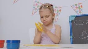 Uma menina bonito pequena que senta-se na tabela no desenho da sala de crian?as com pinturas do dedo manchou suas m?os no amarelo vídeos de arquivo