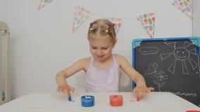 Uma menina bonito pequena que senta-se na tabela tira no papel com as pinturas brilhantes do dedo, mergulhando seus dedos em uns  vídeos de arquivo