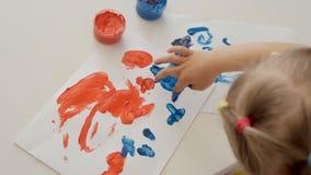 Uma menina bonito pequena que senta-se na tabela tira no papel com as pinturas brilhantes do dedo, mergulhando seus dedos em uns  filme