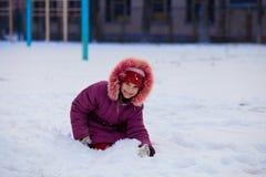 Uma menina bonito que anda no parque da neve Fotos de Stock Royalty Free