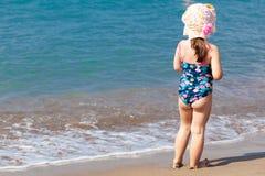 Uma menina bonito que joga na praia do mar foto de stock