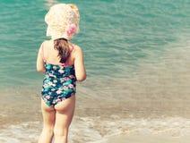 Uma menina bonito que joga na praia do mar imagem de stock royalty free