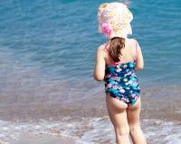 Uma menina bonito que joga na praia do mar fotografia de stock