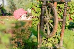 Uma menina bonito senta-se em um feno em uma cesta no jardim Fotografia de Stock