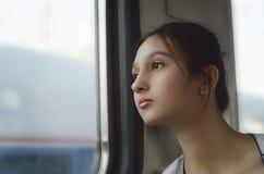 Uma menina bonito viaja pelo trem e olha para fora a janela fotografia de stock royalty free