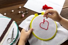 Uma menina borda um coração em uma opinião branca de pano de cima dos acessórios para o bordado no fundo de madeira fotos de stock
