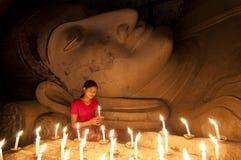 Uma menina burmese bonita para pagar seu respeito à estátua da Buda imagem de stock