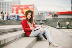 Uma menina caucasiano bonita, nova que senta-se no sorriso da rua, a alegria, senta-se com caderno e pena em Ruhi Na camiseta ver foto de stock