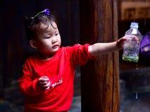 Uma menina chinesa que recebe a água da chuva do telhado imagem de stock