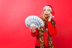 Uma menina chocada em uma camiseta e em um chapéu vermelhos de Santa está falando no telefone e está guardando o dinheiro que des imagem de stock