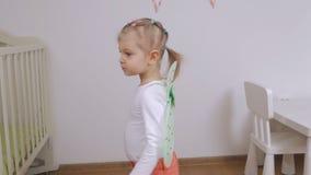 Uma menina com as asas da borboleta do brinquedo atrás de seus giros traseiros na dança video estoque